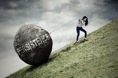 La donna di affari sta scalando con una grande pietra Fotografia Stock Libera da Diritti