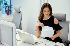 La donna di affari sta sedendosi allo scrittorio con il computer e sta controllando i documenti Immagine Stock