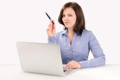 La donna di affari sta sedendosi davanti ad un computer portatile Fotografie Stock