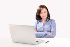 La donna di affari sta sedendosi davanti ad un computer portatile Fotografie Stock Libere da Diritti