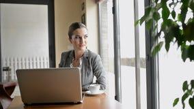 La donna di affari sta sedendosi davanti al computer portatile, aspettante qualcuno video d archivio