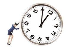 La donna di affari sta spingendo un grande orologio Fotografie Stock Libere da Diritti