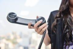 La donna di affari sta tenendo il microtelefono nero del telefono del IP immagine stock libera da diritti
