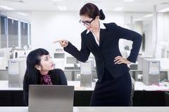 Donna di affari che urla all'impiegato Immagine Stock