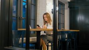 La donna di affari sta utilizzando il App di Smartphone ed il caffè bevente in caffè alla notte video d archivio