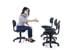 La donna di affari stringe le mani con le sedie vuote Fotografie Stock