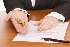 La donna di affari tiene il tasto ed il contratto in mani Fotografie Stock