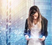 La donna di affari in ufficio si è collegata sulla rete internet con una compressa fotografie stock