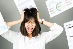 La donna di affari in un vestito bianco è tiro via molto lavoro di ufficio ed i documenti sono spese generali saltate immagine stock