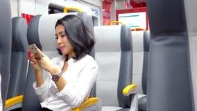 La donna di affari utilizza il cellulare nel treno dell'aeroporto video d archivio