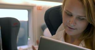 La donna di affari utilizza la compressa elettronica nel treno video d archivio
