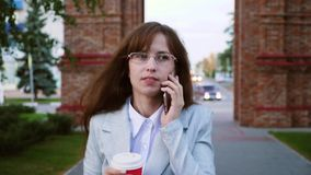 La donna di affari in vetri in vestito leggero va lavorare, la ragazza beve il caffè e parla sullo smartphone archivi video