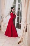 La donna di 30 anni della brunetta elegante adulta in vestito rosso lungo fa una pausa la grande porta della finestra Interno bei Fotografie Stock
