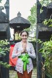 La donna di balinese con i vestiti tradizionali ed il benvenuto gestures lo SMI immagini stock libere da diritti