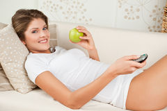 La donna di bellezza sta mangiando la mela verde e la TV di sorveglianza Fotografia Stock Libera da Diritti