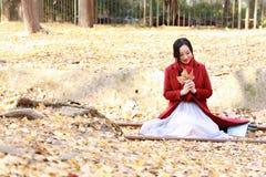 La donna di caduta felice e la beatitudine, bella donna che si siede sull'rotaie in pieno del ginkgo biloba lascia nel parco di a Immagini Stock