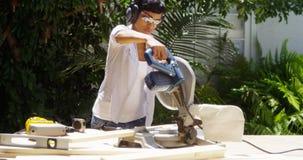 La donna di colore che fa il legno di taglio di miglioramento domestico con una tavola ha visto fotografia stock