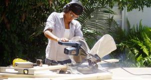 La donna di colore che fa il legno di taglio di miglioramento domestico con una tavola ha visto fotografia stock libera da diritti
