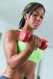 La donna di colore domestica di forma fisica prepara il bicipite con i pesi Fotografia Stock Libera da Diritti