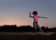 La donna di colore sta facendo allungando il rilassamento ed il riscaldamento di esercizio Fotografie Stock