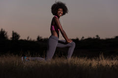 La donna di colore sta facendo allungando il rilassamento ed il riscaldamento di esercizio Immagini Stock