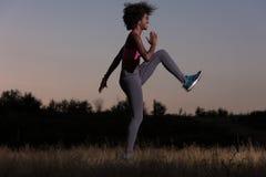 La donna di colore sta facendo allungando il rilassamento ed il riscaldamento di esercizio Immagine Stock
