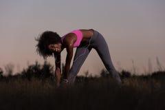 La donna di colore sta facendo allungando il rilassamento ed il riscaldamento di esercizio Fotografia Stock
