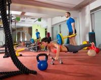 La donna di Crossfit spinge aumenta l'esercizio ed il sollevamento pesi dell'uomo Immagine Stock Libera da Diritti