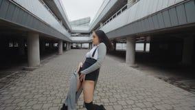 La donna di dancing esegue il ballo moderno di moda, posando, stile libero contemporaneo urbano nel parcheggio archivi video
