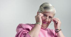 La donna di Eldery mette sopra i vetri sopra e guardando in camera archivi video