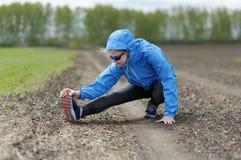 La donna di esercizio che allunga la gamba del tendine del ginocchio muscles il ru all'aperto duing Fotografia Stock Libera da Diritti