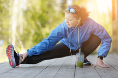 La donna di esercizio che allunga la gamba del tendine del ginocchio muscles il ru all'aperto duing Fotografia Stock