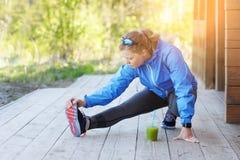 La donna di esercizio che allunga la gamba del tendine del ginocchio muscles il ru all'aperto duing Immagini Stock Libere da Diritti