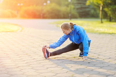 La donna di esercizio che allunga la gamba del tendine del ginocchio muscles il ru all'aperto duing Immagini Stock