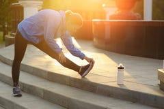 La donna di esercizio che allunga la gamba del tendine del ginocchio muscles il ru all'aperto duing Fotografie Stock Libere da Diritti