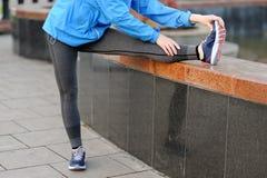 La donna di esercizio che allunga la gamba del tendine del ginocchio muscles il ru all'aperto duing Fotografie Stock