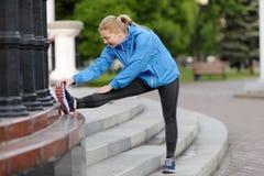 La donna di esercizio che allunga la gamba del tendine del ginocchio muscles il ru all'aperto duing Immagine Stock Libera da Diritti