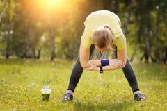 La donna di esercizio che allunga la gamba del tendine del ginocchio muscles il ru all'aperto duing Immagine Stock