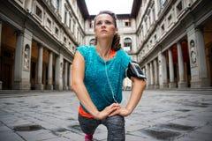 La donna di forma fisica in attrezzatura e nell'insieme sportivi mp3 sta allungando Immagini Stock