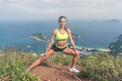 La donna di forma fisica che allunga i suoi muscoli della gamba che fanno l'affondo laterale esercita la preparazione per cardio  Immagine Stock