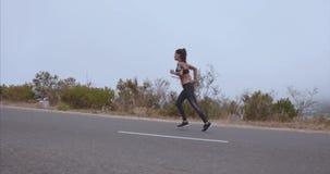 La donna di forma fisica che la inizia funziona sulla strada della campagna stock footage