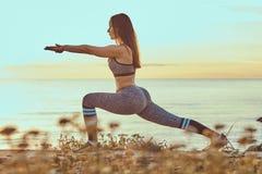 La donna di forma fisica che pratica allungando l'yoga si esercita in natura contro lo sfondo di un mare al tramonto Fotografia Stock