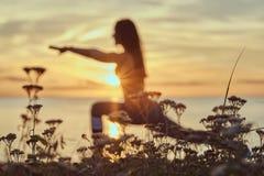 La donna di forma fisica che pratica allungando l'yoga si esercita in natura contro lo sfondo di un mare al tramonto Fotografia Stock Libera da Diritti