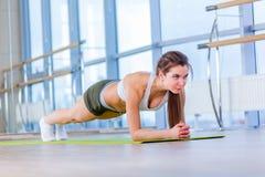 La donna di forma fisica di addestramento che fa l'esercizio del centro della plancia che risolve per i pilates posteriori di con Immagini Stock Libere da Diritti