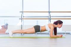 La donna di forma fisica di addestramento che fa l'esercizio del centro della plancia che risolve per i pilates posteriori di con Fotografia Stock Libera da Diritti