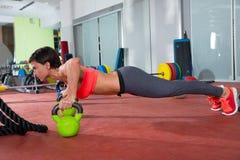 La donna di forma fisica di Crossfit spinge aumenta l'esercizio di piegamento sulle braccia di Kettlebells Fotografie Stock