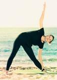 La donna di forma fisica in maglietta nera sta praticando l'insieme di allungamento della e Fotografie Stock Libere da Diritti