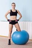 La donna di forma fisica si leva in piedi con la sfera dello svizzero dell'ABS Fotografia Stock