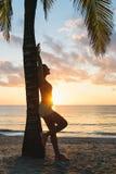 La donna di forma fisica si rilassa dopo l'allenamento tropicale della spiaggia di mattina Immagini Stock Libere da Diritti