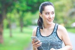 La donna di forma fisica sta ascoltando musica dal suo telefono cellulare mentre Fotografia Stock Libera da Diritti